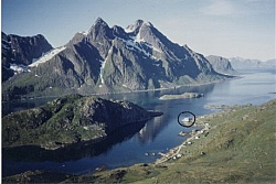 The mighty sea alpine mountains Himmeltindene and the fjord area with the white seahouse Johluns marked with a circle.