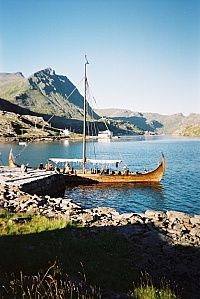 The Viking ship Lofotr, Skarvhellodden. Behind the ship the spacious white seahouse Joh. L. Unstad Sjohus at Maervollpollen, the northern continuation of the fjord Steinfjorden. Reception in the white house (No.205) above the seahouse.